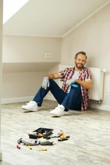 Wazig schot van vrolijke klusjesman die een waterpomptang gebruikt voor het repareren van de radiatorbatterij in de kamer thuis