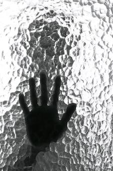 Wazig silhouet van een persoon en zijn hand achter een deur met textuur glas