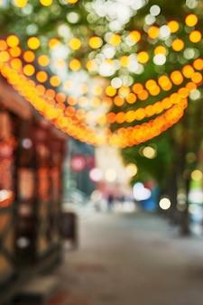 Wazig straat met slingers in de avond