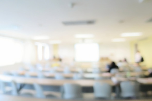 Wazig van collegezaal of vergaderzaal met lange tafel, stoelen, projector en groot raam. onderwijs.