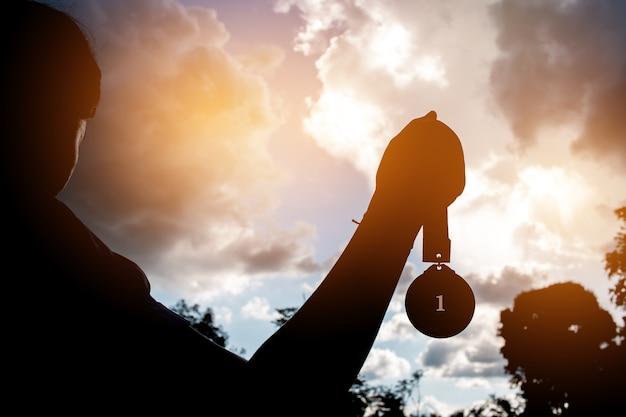 Wazig van silhouet busunesswoman handen opgeheven en houden gouden medailles met lint tegen zonsondergang achtergrond om team succes in het bedrijfsleven, winners succes award concept te tonen.