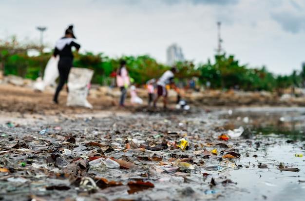Wazig van vrijwilligers die afval verzamelen. strandmilieuvervuiling.