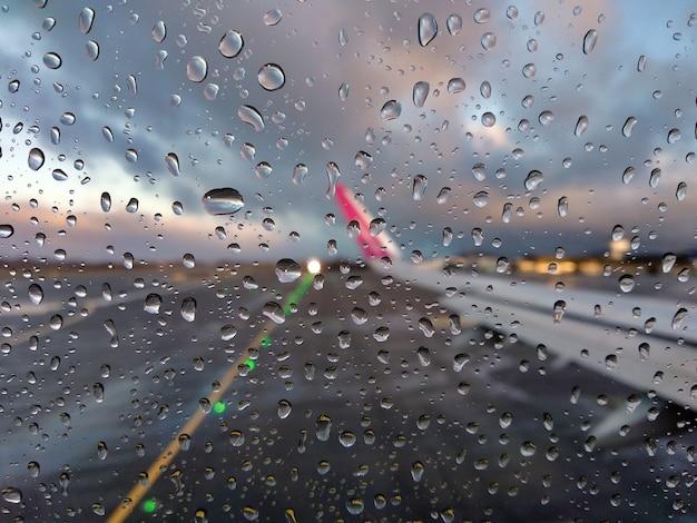 Wazig zicht op de landingsbaan van een luchthaven door het raam van een vliegtuig met regendruppels