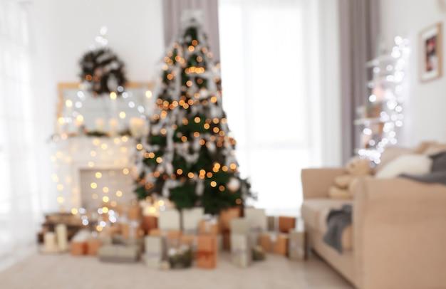Wazig zicht op prachtige dennenboom in ingerichte kamer voor kerstmis