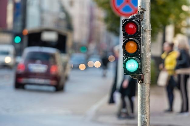 Wazig zicht op stadsverkeer met verkeerslichten, op de voorgrond een seinpaal met groen licht