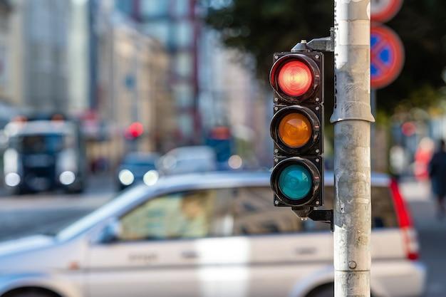 Wazig zicht op stadsverkeer met verkeerslichten, op de voorgrond een verkeerslicht met een rood licht