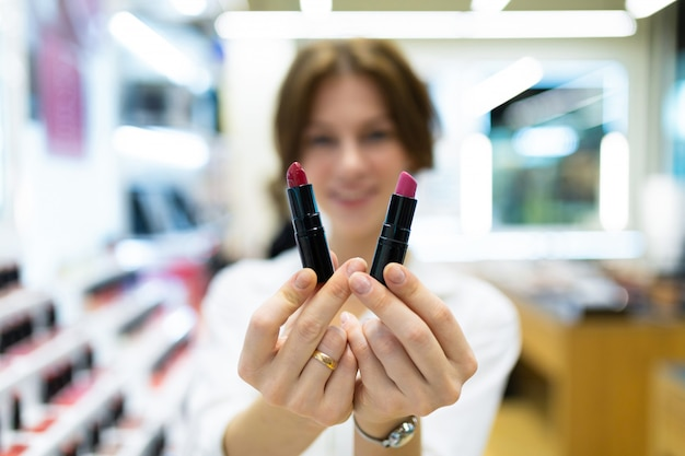Wazig zicht, twee kleurrijke lippenstiften close-up, vrouw met lippenstift