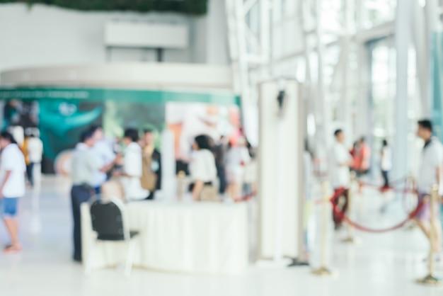 Wazige achtergrond: mensen winkelen op marktbeurs in zonnige dag, vervagen achtergrond met bokeh.