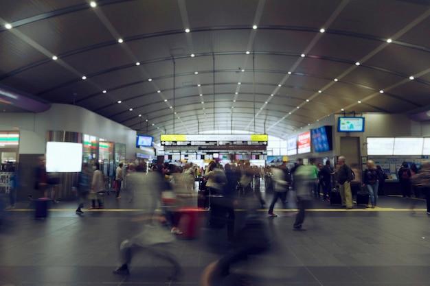 Wazige beweging van mensen die in een modern station lopen