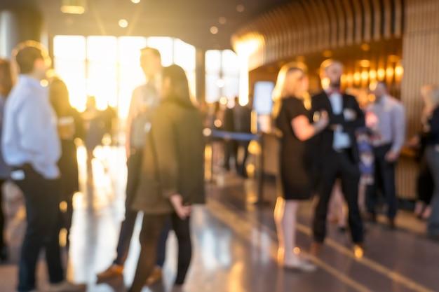 Wazige foto menigte van onherkenbare zakenmensen die staan en samen praten in de tentoonstelling