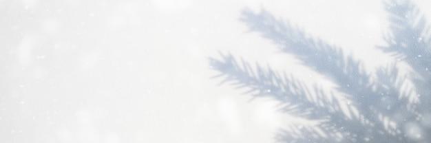 Wazige foto van een schaduw van een kerstboomtak op een witgrijze achtergrond van een muur of tafel. vallende sneeuw. banner