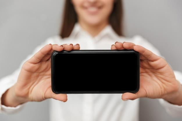 Wazige foto van lachende vrouw met lang bruin haar met mobiele telefoon en reclame zwart copyspace scherm in focus close-up, geïsoleerd over grijze muur