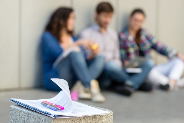 Wazige foto van mensen met boeken en gadgets op de vloer vlakbij de muur zitten. onderwijs social media concept.