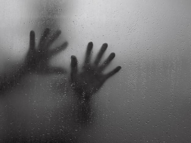 Wazige hand schaduw achter de spiegel