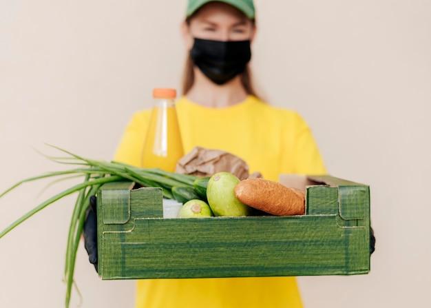 Wazige levering vrouw met voedselkrat