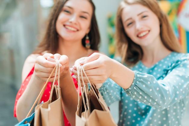 Wazige meisjes die boodschappentassen