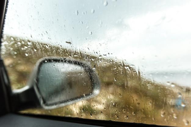 Wazige regendaling op de achtergrond van het autoglas, waterdalingen bij het autoraam
