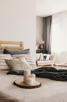 Wazige voorgrond met kaarsen op houten kofferbak in echte foto van lichte open ruimte slaapkamer interieur met raam met gordijnen en bank