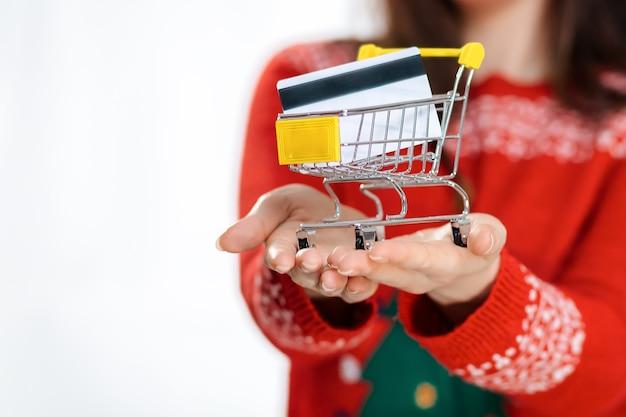 Wazige vrouw in een nieuwjaarssweater, met een minikarretje met een bankkaart. handen sluiten omhoog. witte achtergrond. het concept van de kerstverkoop.