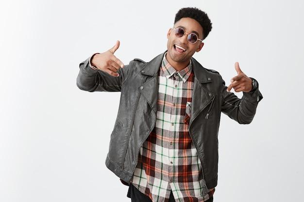 Wazzup man. aantrekkelijke jonge donkere man met afro kapsel in zwarte leren jas en zonnebril lachen, gebarend met handen, dansen en zingen op feestje, met plezier.