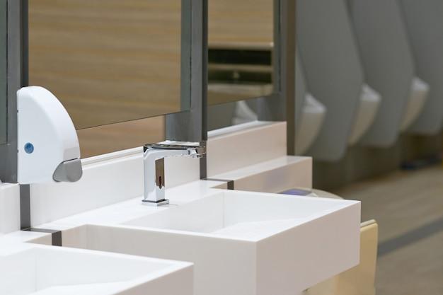 Wc-gootsteen voor washand met zeepdaling op onduidelijk beeld urinoirachtergrond
