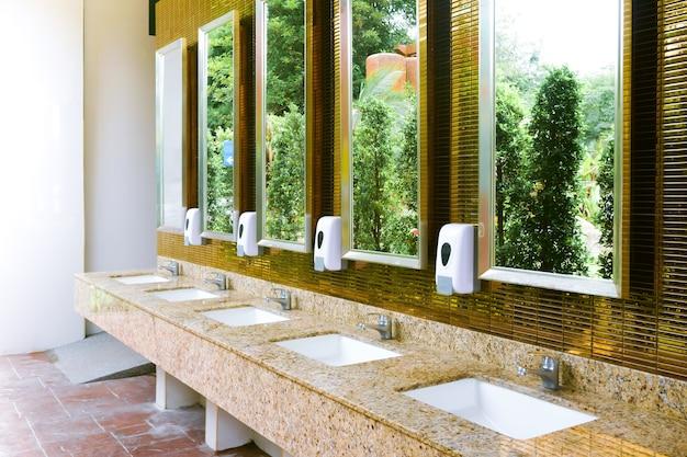 Wc-gootsteenbinnenland van openbaar toilet met handen wassen en gouden spiegel
