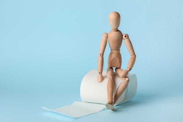 Wc-papier met houten menselijke figuur op kleur