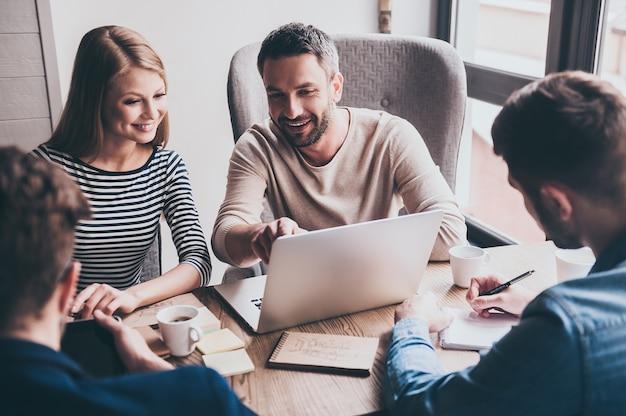 We hebben een positieve dynamiek! jonge knappe man wijzend op zijn laptop met een glimlach terwijl hij aan de kantoortafel zit op een zakelijke bijeenkomst met zijn collega's