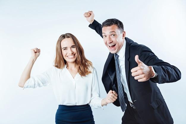 We hebben het gedaan. zeer gelukkige zakenmensen die hun vuisten opheffen en wijd in de camera grijnzen terwijl ze hun succes vieren.