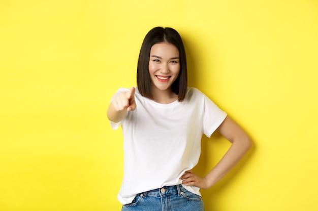 We hebben u nodig. zelfverzekerde aziatische vrouw glimlachend, wijzende vinger op camera, uitnodigend om met haar mee te doen, te wenken of iemand te kiezen, staande op gele achtergrond.