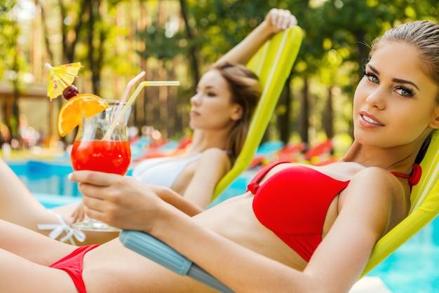 We houden ervan om tijd aan het zwembad door te brengen. zijaanzicht van twee aantrekkelijke jonge vrouwen in bikini die cocktails drinken terwijl ze ontspannen in een ligstoel bij het zwembad