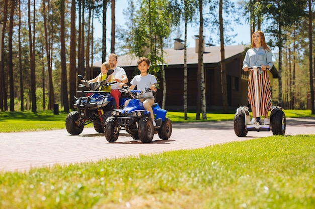 We houden van snelheid. geïnspireerde schattige kinderen die tijd doorbrengen met hun ouders en atv's besturen