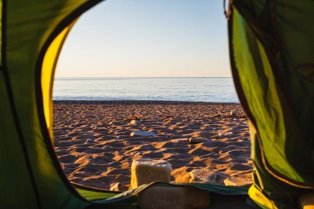 We kijken vanuit de tent naar de zee