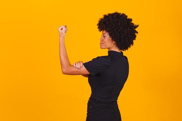 We kunnen het. vrouwenvuist van vrouwelijke kracht. vrouw slachtoffer van racisme. misbruik op het werk. de vrouwelijke kracht. vrouwelijke empowerment. de kracht van vrouwen. gele achtergrond.