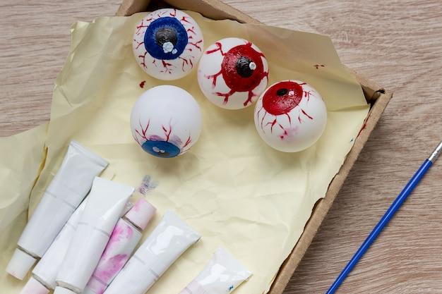 We maken een decor voor halloween, schilderen een oogbol op een tennisbal met verf. diy knutselen met kinderen