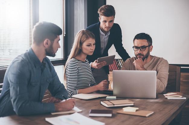 We moeten dit document doornemen! peinzende jonge knappe man die naar laptop kijkt terwijl hij aan de kantoortafel zit op een zakelijke bijeenkomst met zijn collega's