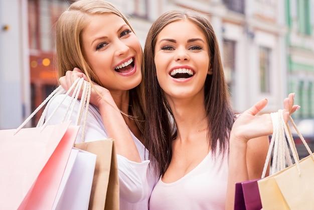 We vinden het heerlijk om samen te winkelen. twee gelukkige jonge vrouwen die boodschappentassen vasthouden en glimlachen terwijl ze buiten staan