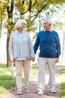 We vinden het heerlijk om tijd samen door te brengen. gelukkig senior paar hand in hand en glimlachen tijdens het wandelen door de parkpas manier samen
