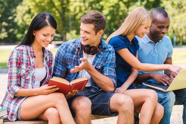 We vinden het heerlijk om tijd samen door te brengen. vier gelukkige jonge mensen die samen tijd doorbrengen terwijl ze buiten zitten