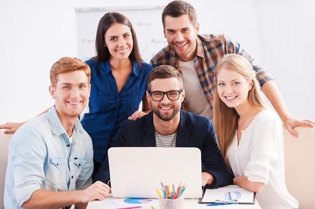 We werken als team. groep vrolijke zakenmensen in slimme vrijetijdskleding die samenwerken en glimlachen