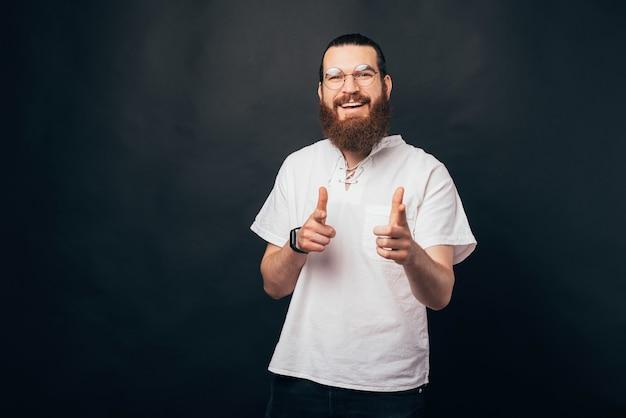 We willen jou voor deze baan. bebaarde man wijst met beide handen naar de camera.