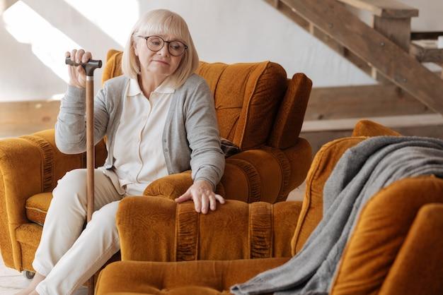We zaten hier vroeger samen. depressieve, ongelukkige oudere vrouw die een wandelstok vasthoudt en naar de lege ruimte naast haar kijkt terwijl ze treurt om haar man