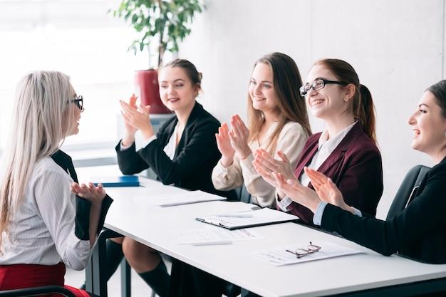 We zijn aan het huren. succesvol sollicitatiegesprek. klappende hr-vrouwen kijken naar vrouwelijke sollicitant
