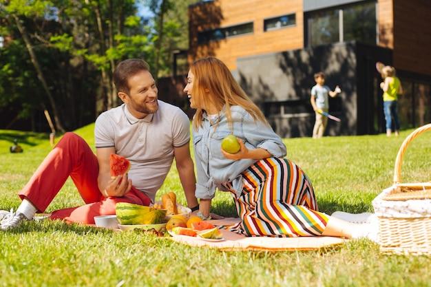 We zijn gelukkig. vrolijke bebaarde man watermeloen houden en praten met zijn vrouw