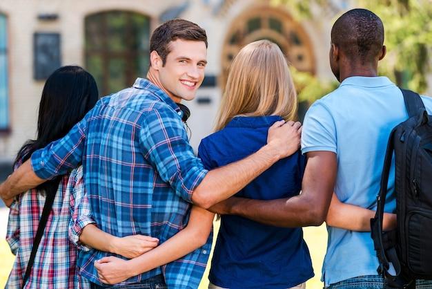 We zijn goede vrienden. achteraanzicht van een knappe jongeman die over de schouder kijkt en glimlacht terwijl hij samen met vrienden loopt