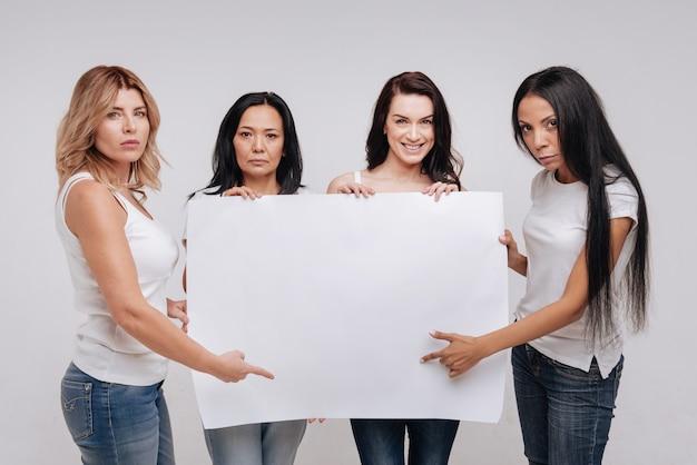 We zijn hier voor een goed doel. inspirerende sterke prachtige dames die een grote lege poster demonstreren tijdens het poseren