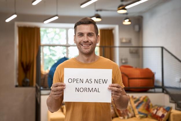 We zijn open jonge, gelukkige kantoormedewerker die papier toont met tekst open als nieuw normaal en glimlacht naar