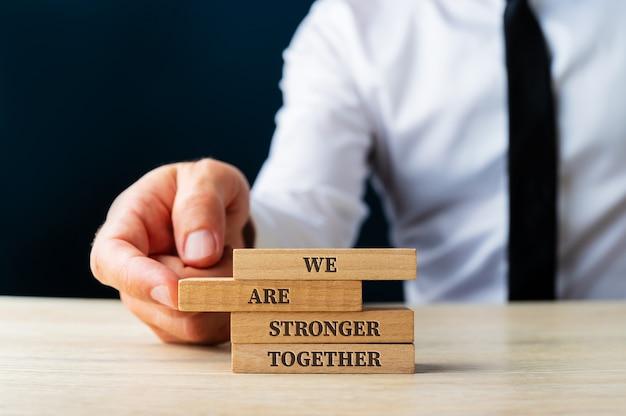 We zijn samen sterker ondertekenen op houten pinnen die worden gestapeld door een zakenman in een conceptueel beeld.