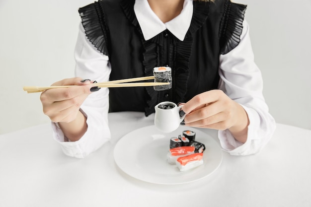 We zijn wat we eten. close-up van het eten van voedsel van de vrouw gemaakt van plastic, eco-concept. er zijn zoveel polymeren dat we er gewoon van gemaakt zijn. milieuramp, mode, schoonheid. organische wereld verliezen.