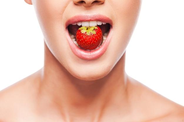 We zijn wat we eten. close-up van mooie jonge shirtloze vrouw die aardbei in haar mond houdt terwijl ze tegen een witte achtergrond staat